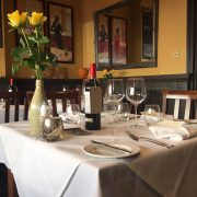Oscar's tables dressed in white linen with cutlery, wine glasses and flowers on the tables