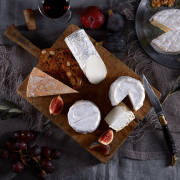 cheese on a wooden board including a goats cheese and bunch of grapes
